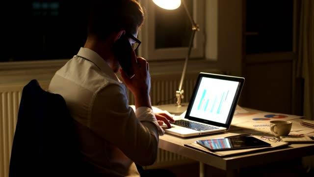 vidéos et rushes de l'homme d'affaires, parler de téléphone à la recherche par le biais de documents - notaire