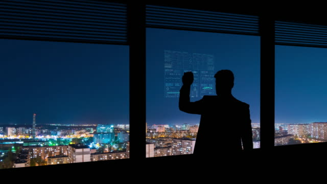 the businessman working on a virtual display on the night urban background - man look sky scraper video stock e b–roll