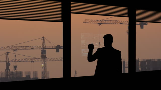 the businessman working on a virtual screen on building construction background - man look sky scraper video stock e b–roll