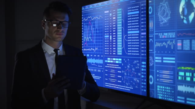 The businessman working with tablet and monitors in a lab