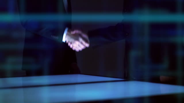 the businessmen handshake above a screen on a hologram background. slow motion - fiducia video stock e b–roll