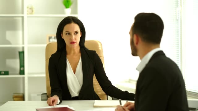 The businesswoman interviews a man at the office table