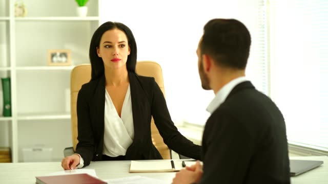 The businesswoman interviews a man at the table
