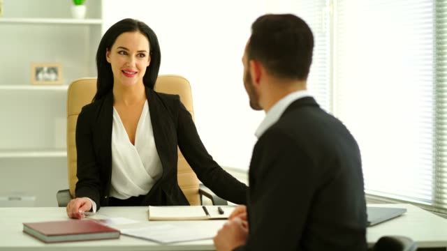 The businesswoman interviews a man in the office room