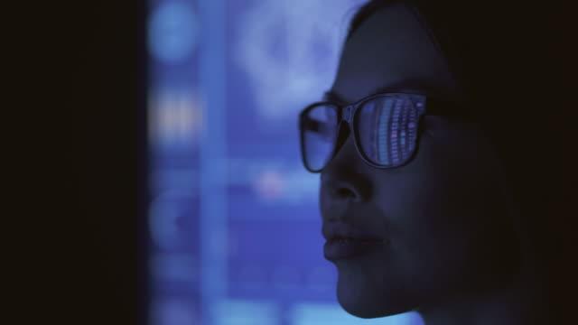 die geschäftsfrau schaut auf den blauen bildschirm im dunklen labor - börsenhandel finanzberuf stock-videos und b-roll-filmmaterial