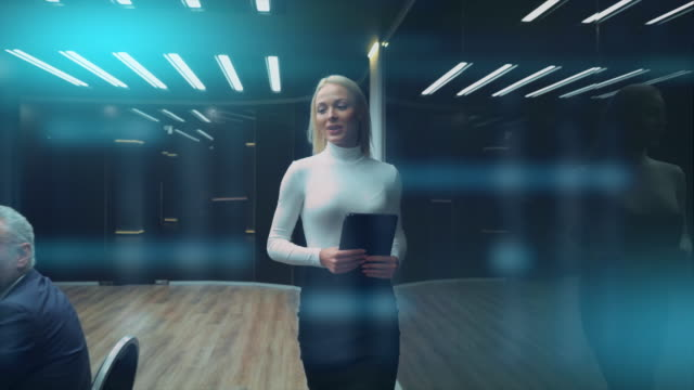 The businesswoman walking into the room and talks to partners. slow motion The businesswoman walking into the room and talks to partners. slow motion grace stock videos & royalty-free footage
