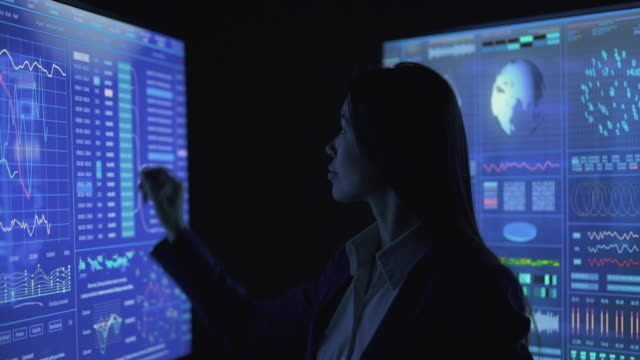 The businesswoman working on the blue sensor screen in the dark lab