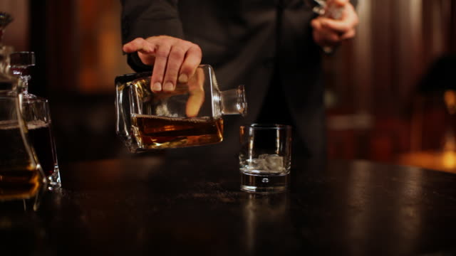 The butler fills whiskey glass, having a closer look video