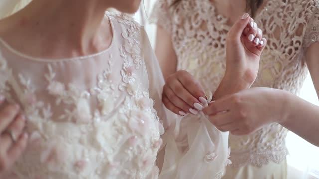 Se sujetan los botones del vestido de boda de Dama de honor. Reunión de mañana de la novia - vídeo