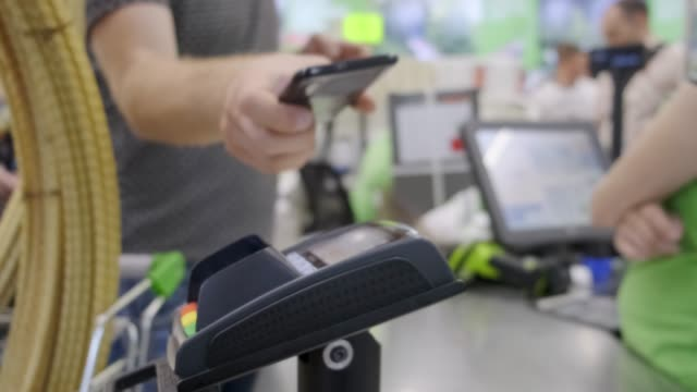 vídeos de stock e filmes b-roll de the buyer in the store pays for the goods by phone, contactless payment. - paying with card contactless