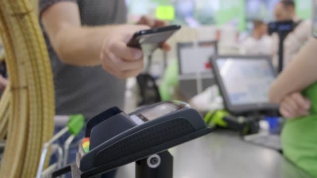 vidéos et rushes de l'acheteur dans le magasin paie pour les marchandises par téléphone, paiement sans contact. - pay