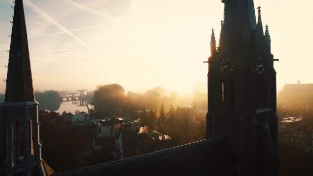 The Camera flies between two towers of a church on a foggy morning AERIAL: The Camera flies between two towers of a church on a foggy morning with godrays in a small town. 4K / UHD / Ultra HD netherlands stock videos & royalty-free footage
