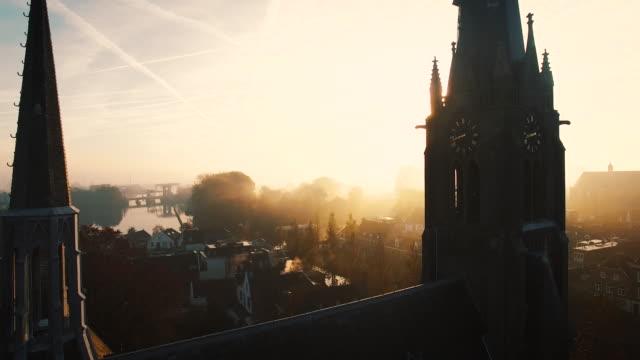 stockvideo's en b-roll-footage met de camera vliegt tussen de twee torens van een kerk op een mistige ochtend - netherlands
