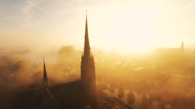 The camera flies towards a church covered in fog video
