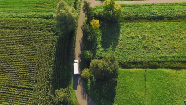 The camera follows a white van driving from the top on a small road through video