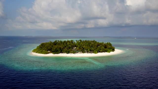 カメラがモルディブ、fullhd で上からのドローン映像空中写真で白い砂のヤシの木とターコイズ、インド洋ラウンド熱帯の島のリゾート ホテルに近づいています。 - ヴィラ点の映像素材/bロール