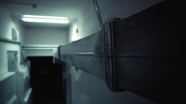 The camera moves along an old ventilation pipe in a dark basement. video