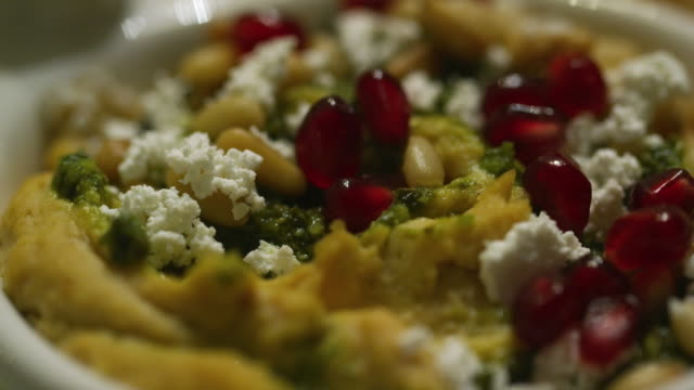 The Camera Pans an Up-Close Shot of a Hummus Appetizer with Feta Cheese, Pine Nuts, Spinach, and Pomegranate Arils (Seeds) at an Indoor Celebration/Party The Camera Pans an Up-Close Shot of a Hummus Appetizer with Feta Cheese, Pine Nuts, Spinach, and Pomegranate Arils (Seeds) at an Indoor Celebration/Party garnish stock videos & royalty-free footage