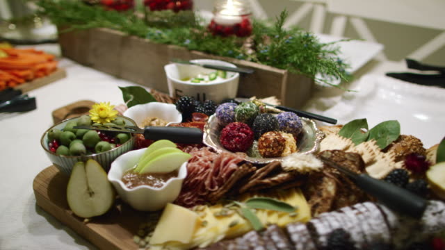 The Camera Pans Around an Appetizer Charcuterie Meat/Cheeseboard with Various Fruit, Sauces, and Garnishes on a Table at an Indoor Christmas Celebration/Party
