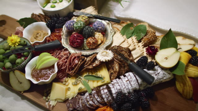 the camera pans around an appetizer charcuterie meat/cheeseboard with various fruit, sauces, and garnishes on a table at an indoor celebration/party - taca filmów i materiałów b-roll