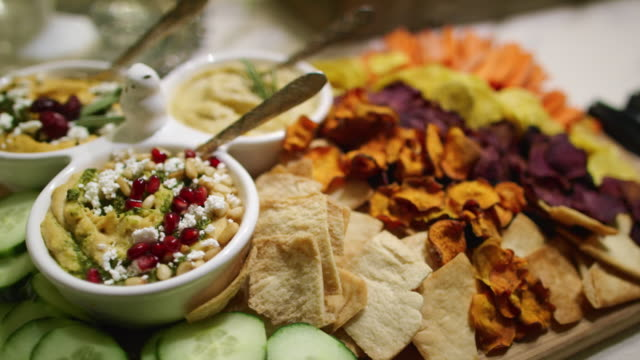 The Camera Pans Around Various Dips, Appetizers, Fruits, Cucumbers, Beet Crisps, Crackers, and Hummuses in Bowls on a Cutting Board on a Table at an Indoor Celebration/Party