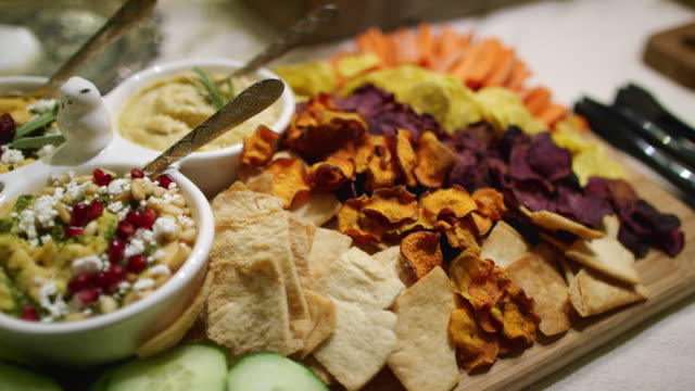 the camera pans around various dips, appetizers, fruits, cucumbers, beet crisps, crackers, and hummuses in bowls on a cutting board on a table at an indoor celebration/party - buffet video stock e b–roll