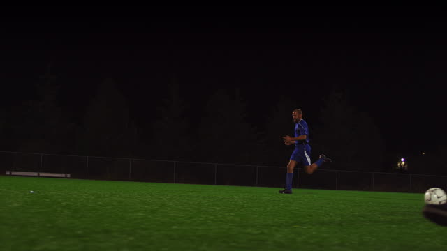 The camera pans with a soccer team as they shoot and the goalie blocks a goal, in slow motion video