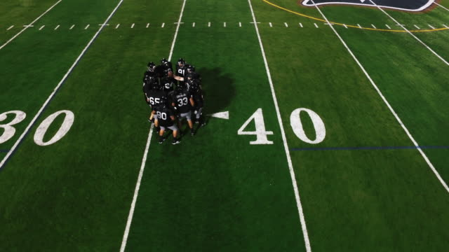 The camera spins from above as a football team in a huddle gets hyped and runs onto the field video