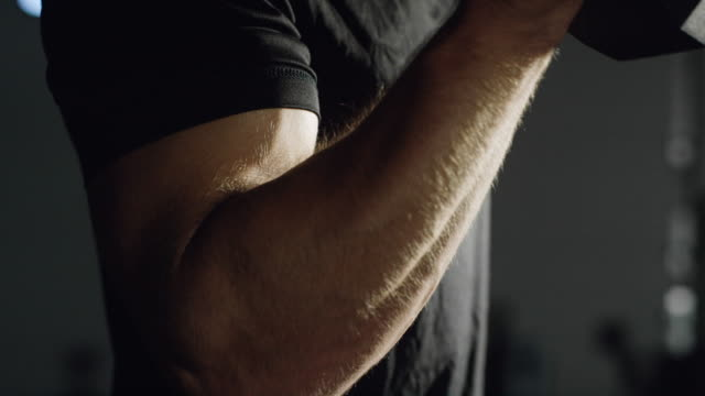 The Camera Tilts Down as an Attractive Caucasian Man in His Twenties with a Beard Performs Bicep Curls with a Dumbbell in a Dramatically Lit Gym (tight shot) The Camera Tilts Down as an Attractive Caucasian Man in His Twenties with a Beard Performs Bicep Curls with a Dumbbell in a Dramatically Lit Gym (tight shot) bent stock videos & royalty-free footage