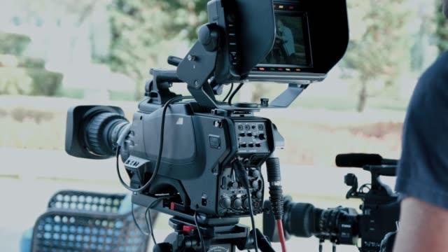 vidéos et rushes de le caméraman zoome et se concentre avec son appareil photo sur l'émission de télévision. industrie cinématographique et télévisuelle - interview