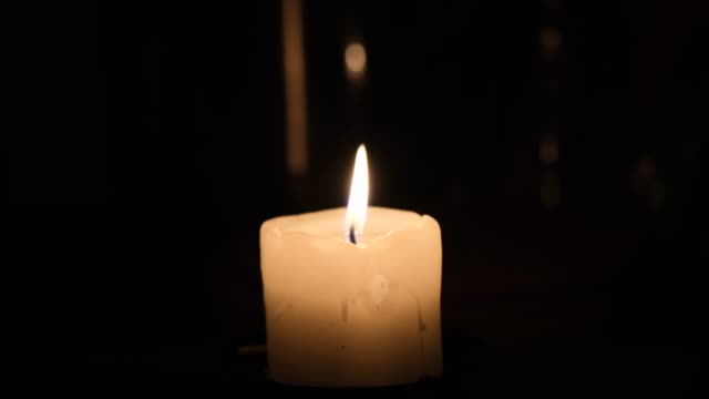 The candle burns and goes out on a black background. Close up. Flames sway in the wind from the draft. A romantic evening by candlelight.