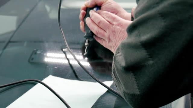 vidéos et rushes de le spécialiste de la réparation automobile verre difficulté vitres automobiles. - image teintée
