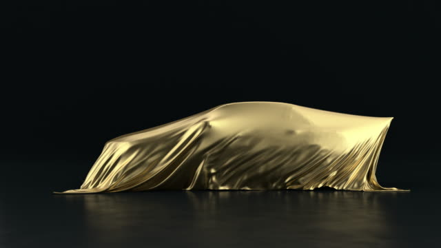 the car is covered with a gold cloth on a black background. the fabric falls from the vehicle but under it is nothing. - coprire video stock e b–roll