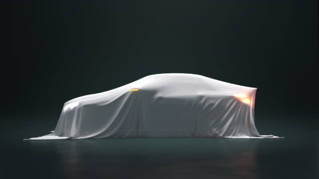 The car is covered with a white cloth on a black background. The fabric falls from the vehicle but under it is nothing.