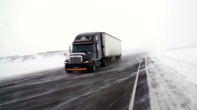 The car is on a snow-covered highway. Heavy truck with trailer carries cargo.
