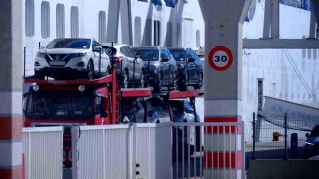 The car transporter leaves the territory of the cargo sea port of Valencia The car transporter leaves the territory of the cargo sea port of Valencia fully loaded with new cars imported from Japan car transporter stock videos & royalty-free footage