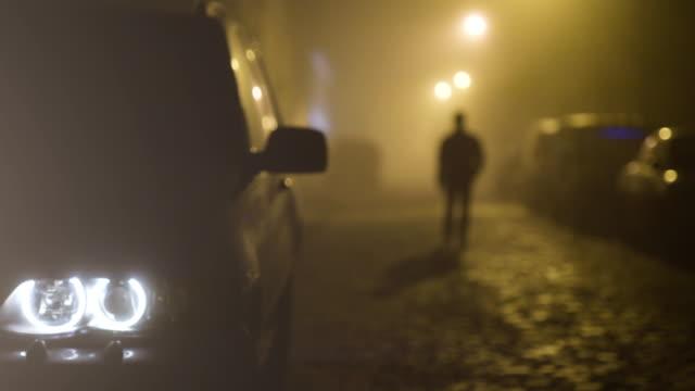 stockvideo's en b-roll-footage met de auto met een koplamp op de walking man achtergrond. avond nacht tijd - mist donker auto