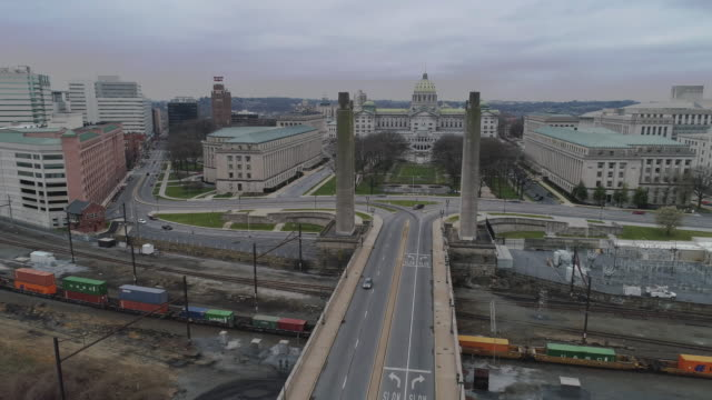 The cargo train passing in front of the Pennsylvania State Capitol Complex trough the industrial zone which is now deserted because of COVID-19 Novel Coronavirus Outbreak.  Drone video with the panoramic camera motion.