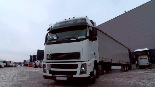 vídeos de stock, filmes e b-roll de o caminhão da carga da cor branca carregou e conduz lentamente fora do complexo do armazém no inverno - carregamento atividade