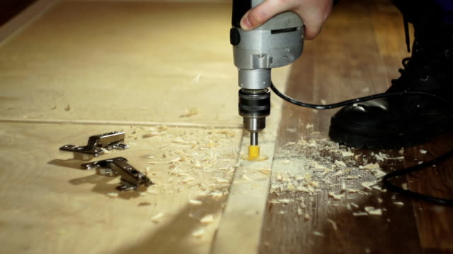 The carpenter drills a hole in the wooden door to install the hinges video