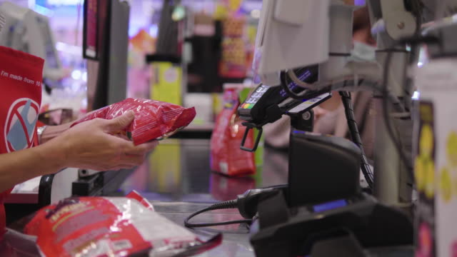 The cashier woman is scanning the item at the checkout counter