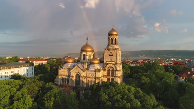 the cathedral of the assumption in varna, bulgaria and colorful rainbow. aerial drone view. - bułgaria filmów i materiałów b-roll