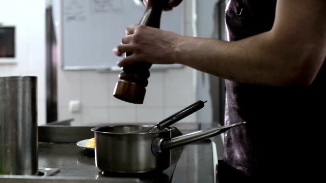 The chef adds spices and pepper to the saucepan with sauce - video