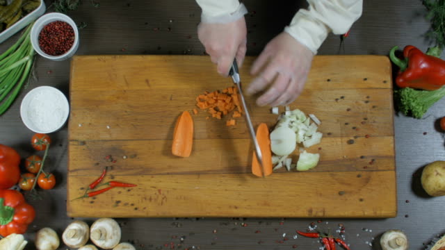 The chef cuts onions and carrots. Onions and carrots as an ingredient for making soup or another dish. Top view video