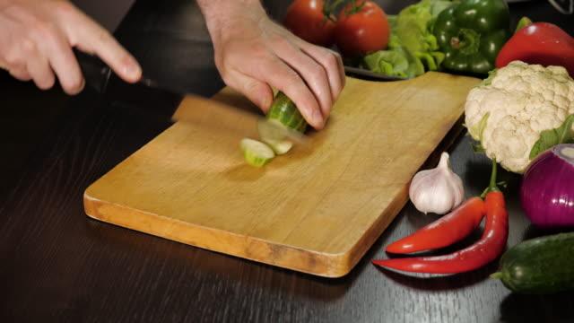 The chef cuts the cucumber.