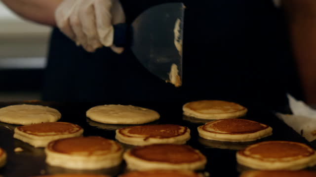 the chef makes pancakes for breakfast at the buffet restaurant. the process of making pancakes on a large oven. - pancake video stock e b–roll