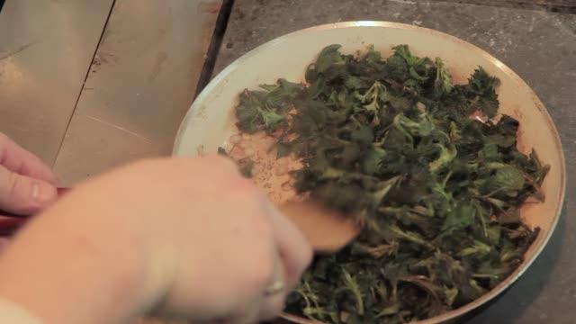 vídeos y material grabado en eventos de stock de el chef pone las hojas de la ortiga en la sartén de la cocina del restaurante. chef remueve y papas fritas ortiga silvestre en la sartén como un garnir para pescar comida - cocina doméstica