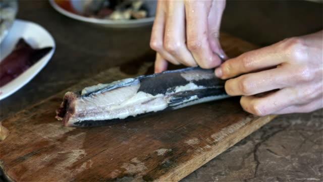 シェフは、サラダに魚から皮膚を削除します。 ビデオ