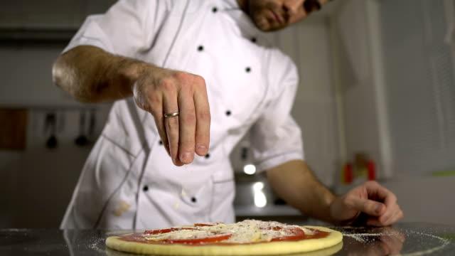 kocken strössel kryddor på den färdiga pizzan i köket - confetti bildbanksvideor och videomaterial från bakom kulisserna