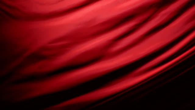 ドラマチックな照明の下で黒の背景に光の赤い生地の動く折り目のシックでエレガントな質感。スローモーション 200 fps - チュール生地点の映像素材/bロール